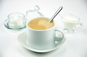 Coffee in a white cup served on a saucer with stirring spoon.