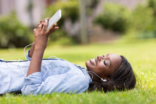 36660772 - relaxed african woman lying on grass listening to music