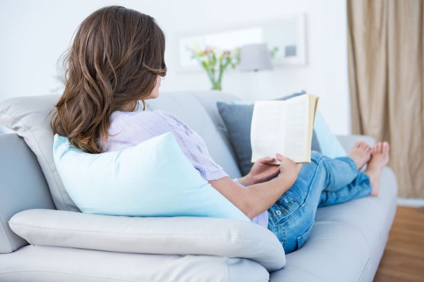 39829538 - woman reading book on couch at home in the living room