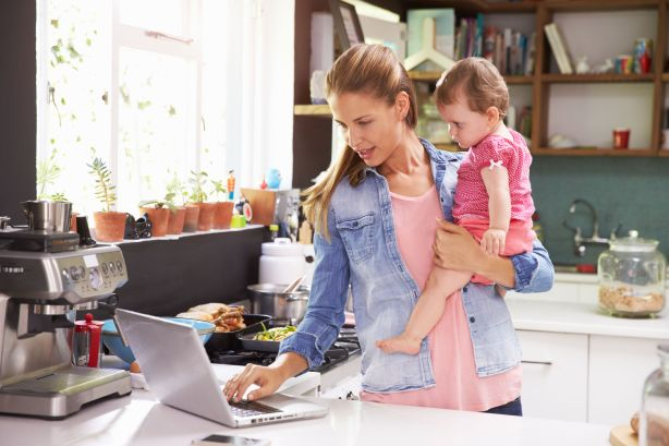 41402478 - mother with young daughter using laptop in kitchen