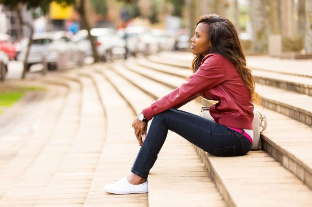 30685198 - thoughtful young african woman sitting outdoors